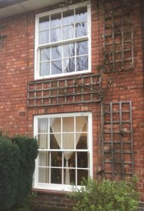two ultimate rose sash windows in a redbrick wall exterior