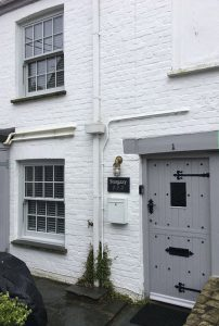White brick cottage with grey sliding sash windows
