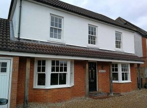 a two storey house exterior with bay and sash windows fitted