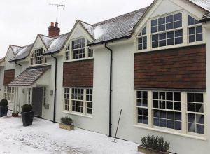 Snow outside house with cream sliding sash windows