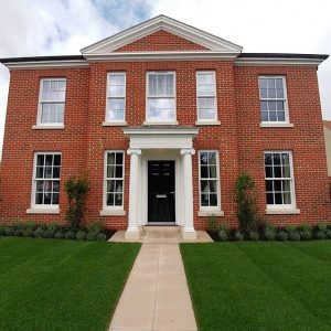 Heritage rose windows on bespoke red brick house