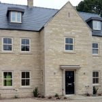 Sandstone detached house with cream sliding sash windows